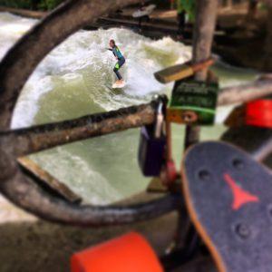 Surferin auf dem Eisbach mit unscharfem BoostedBoard im Vordergrund